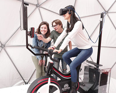 some people testing out a virtual reality bike