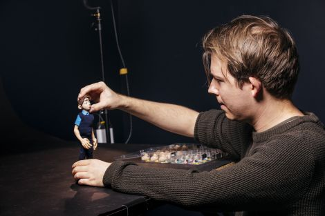 Student working with a character in the stop motion studio