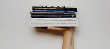 A hand holding books
