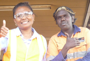 Two Indigenous workers giving the thumbs up