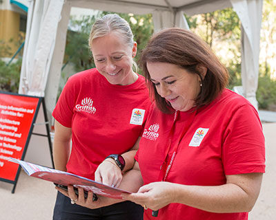 Griffith staff dressed in red, reading an information brochure